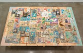 Kristen Morgin<br /> <i>The Repeating Table</i>, 2010<br /> Wood, books, toys, records with clay painted counterparts<br /> 45 x 68 x 108 inches<br /> 114.3 x 172.7 x 274.3 cm<br />